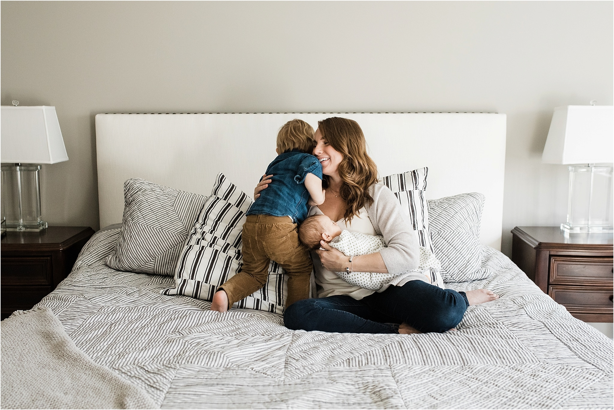 toddler kissing mother holding new brother