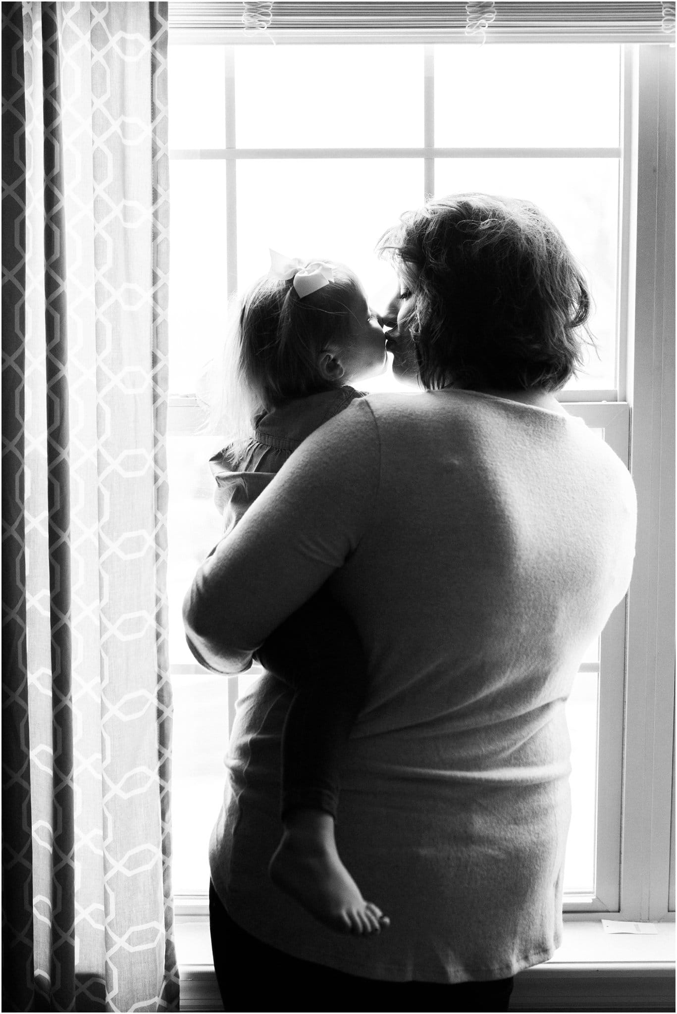 mother holding and kissing daughter