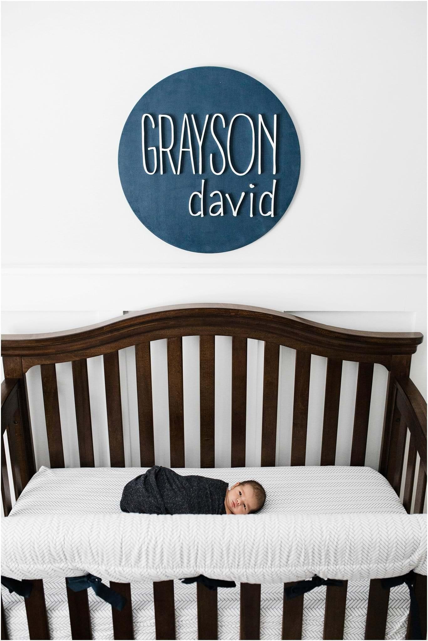 newborn baby swaddled in crib