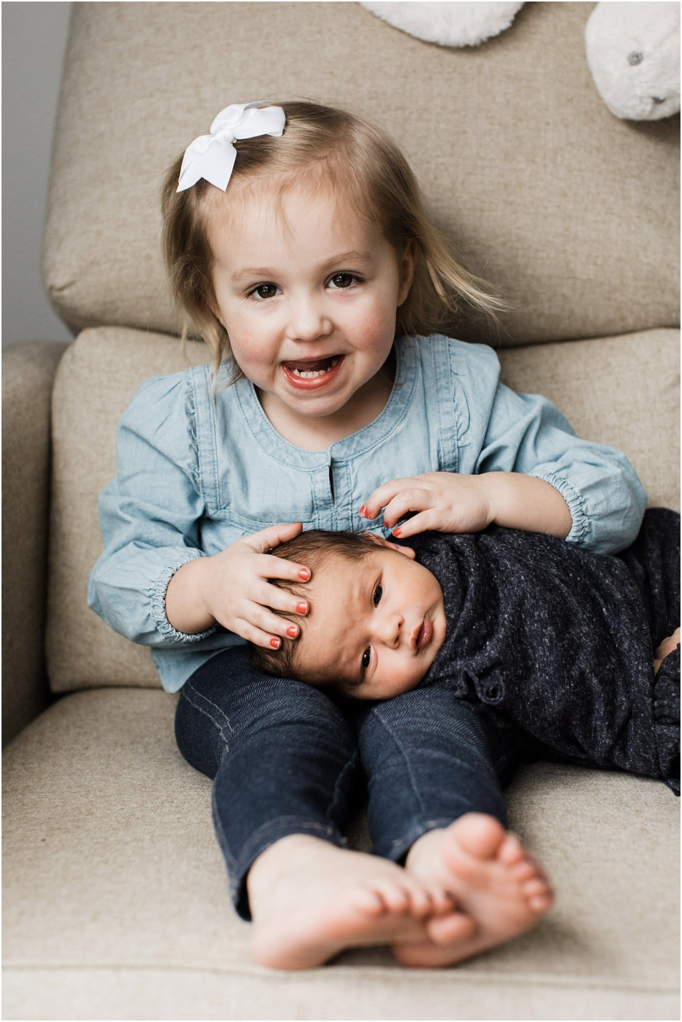 big sister with newborn baby brother on chair in nursery
