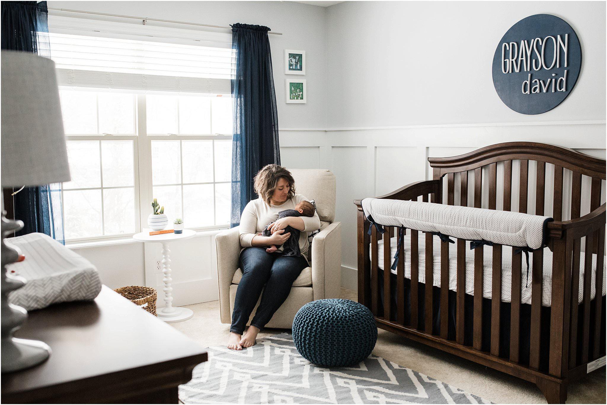 mother holding newborn in navy nursery