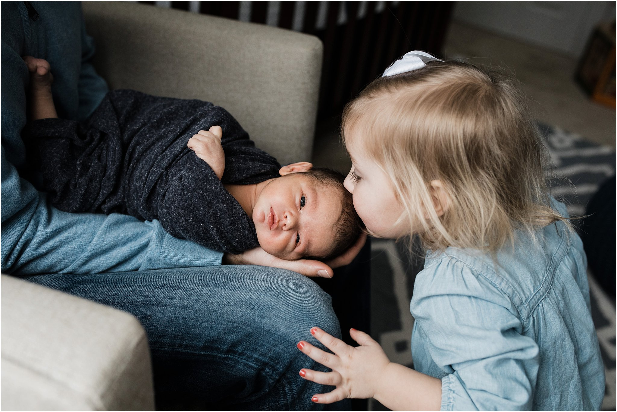 big sister kissing newborn brother