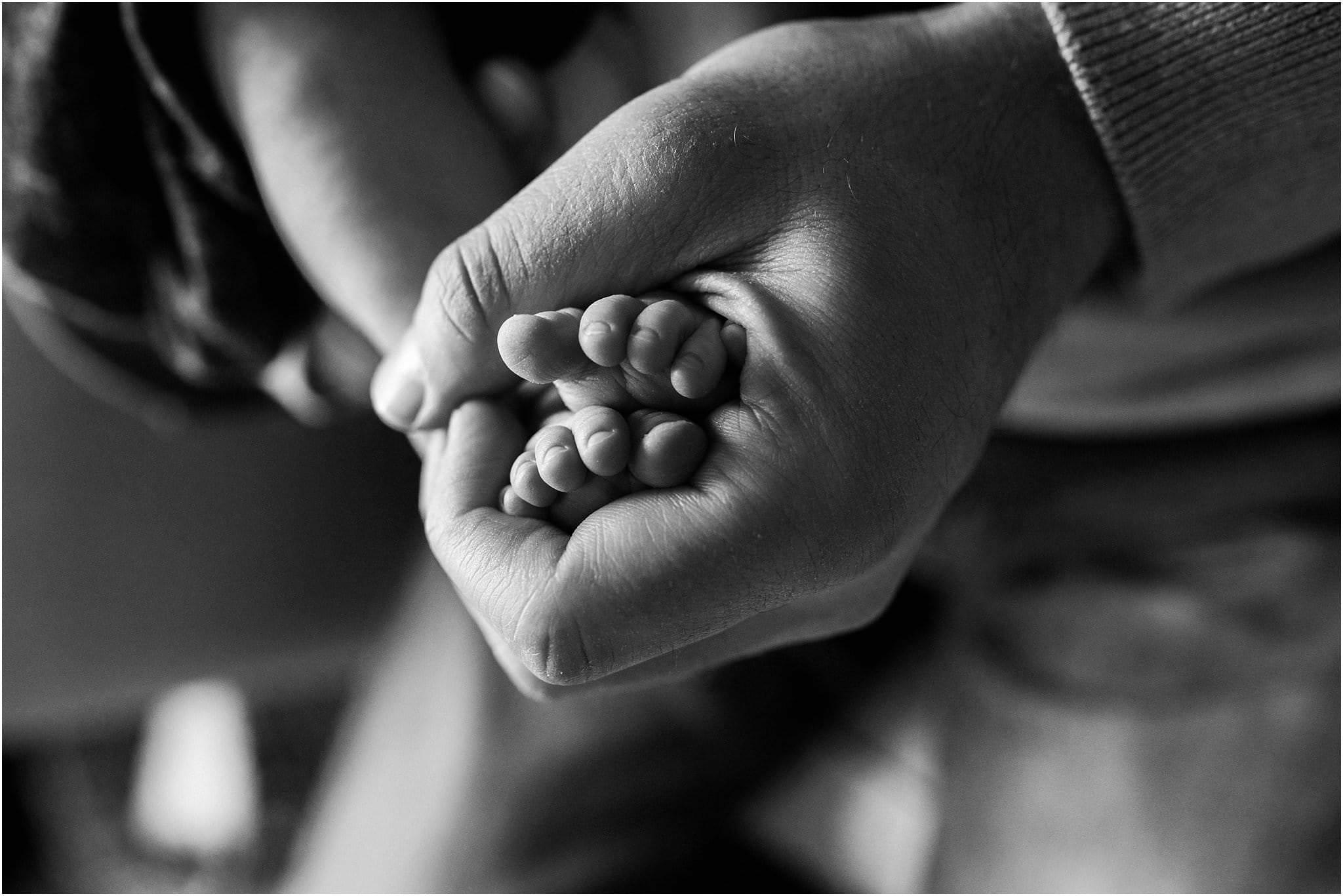 fathers hands holding newborn feet
