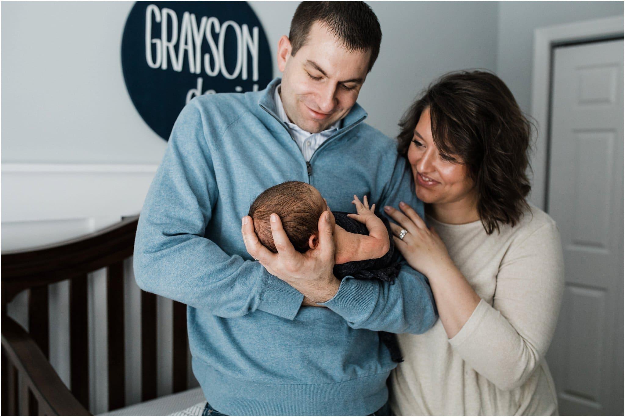 parents holding newborn son in nursery