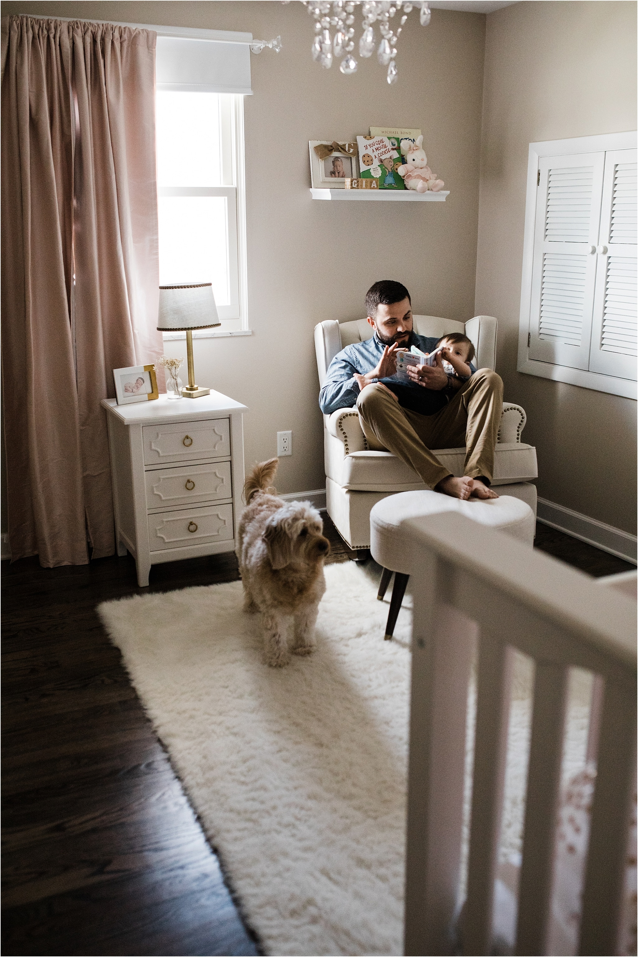 FATHER READING TO ONE YEAR IN HER NURSERY