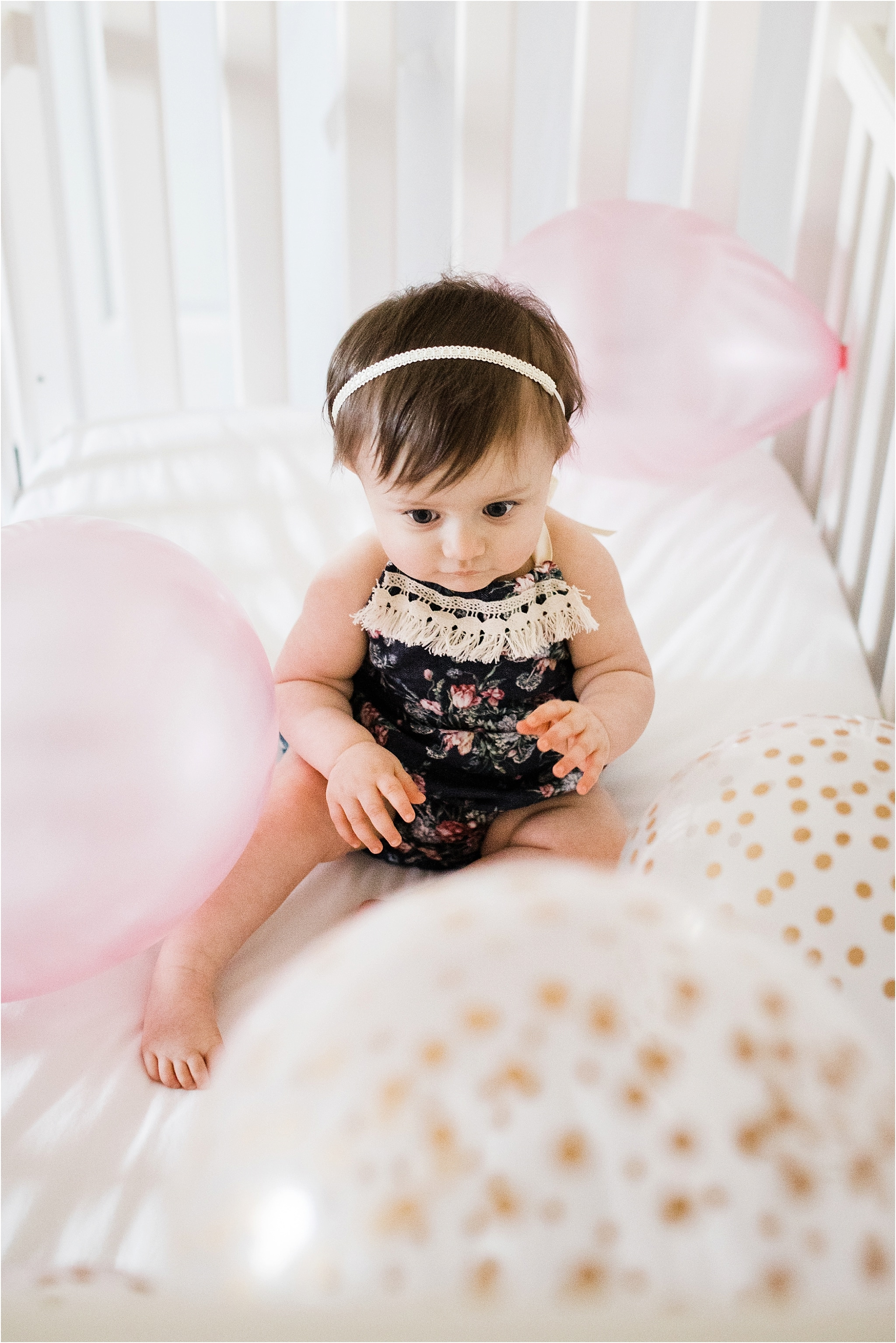 ONE YEAR OLD GIRL IN FLORAL ROMPER PHOTOS IN NURSERY WITH BALLOONS