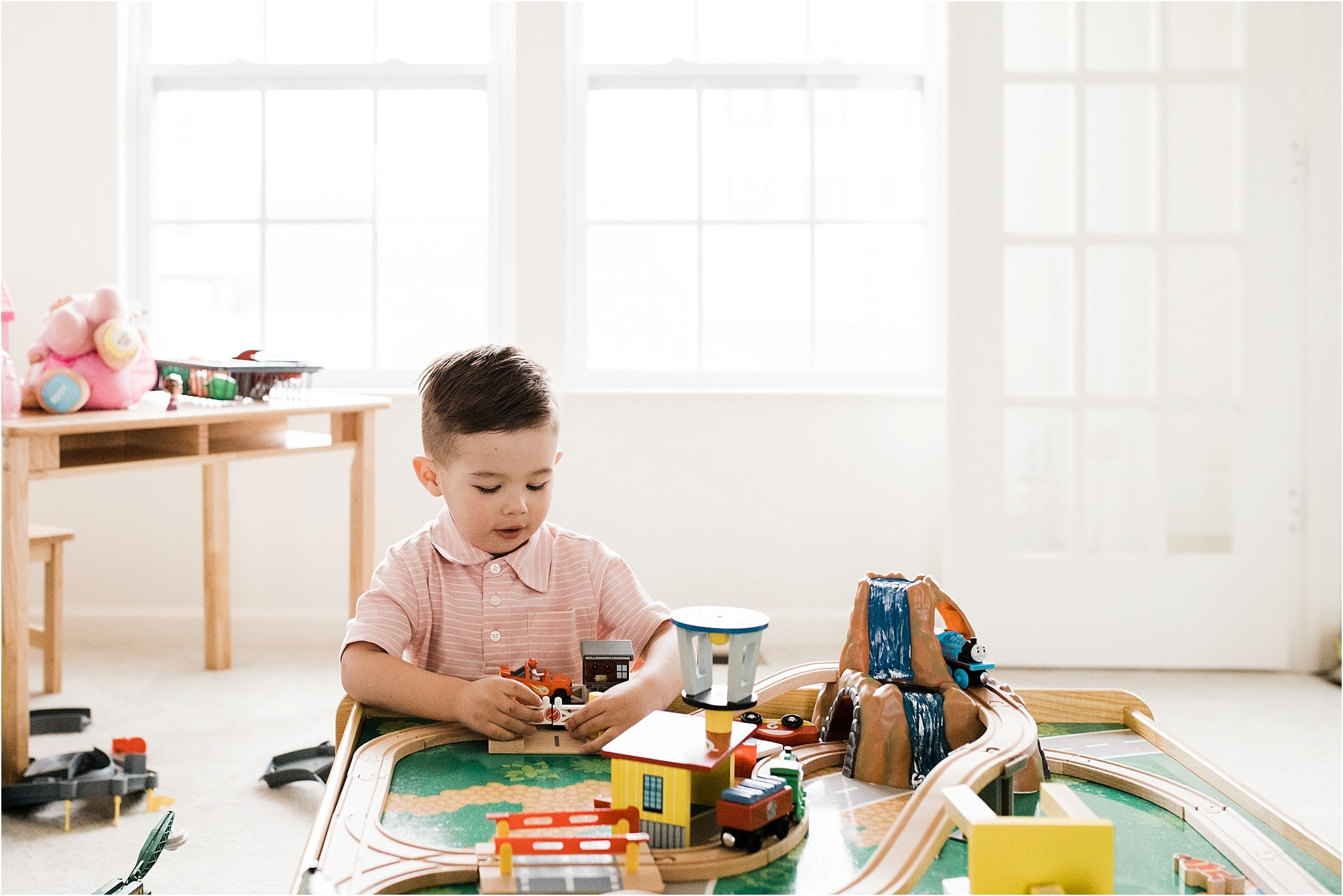 boy playing with trains in family playroom