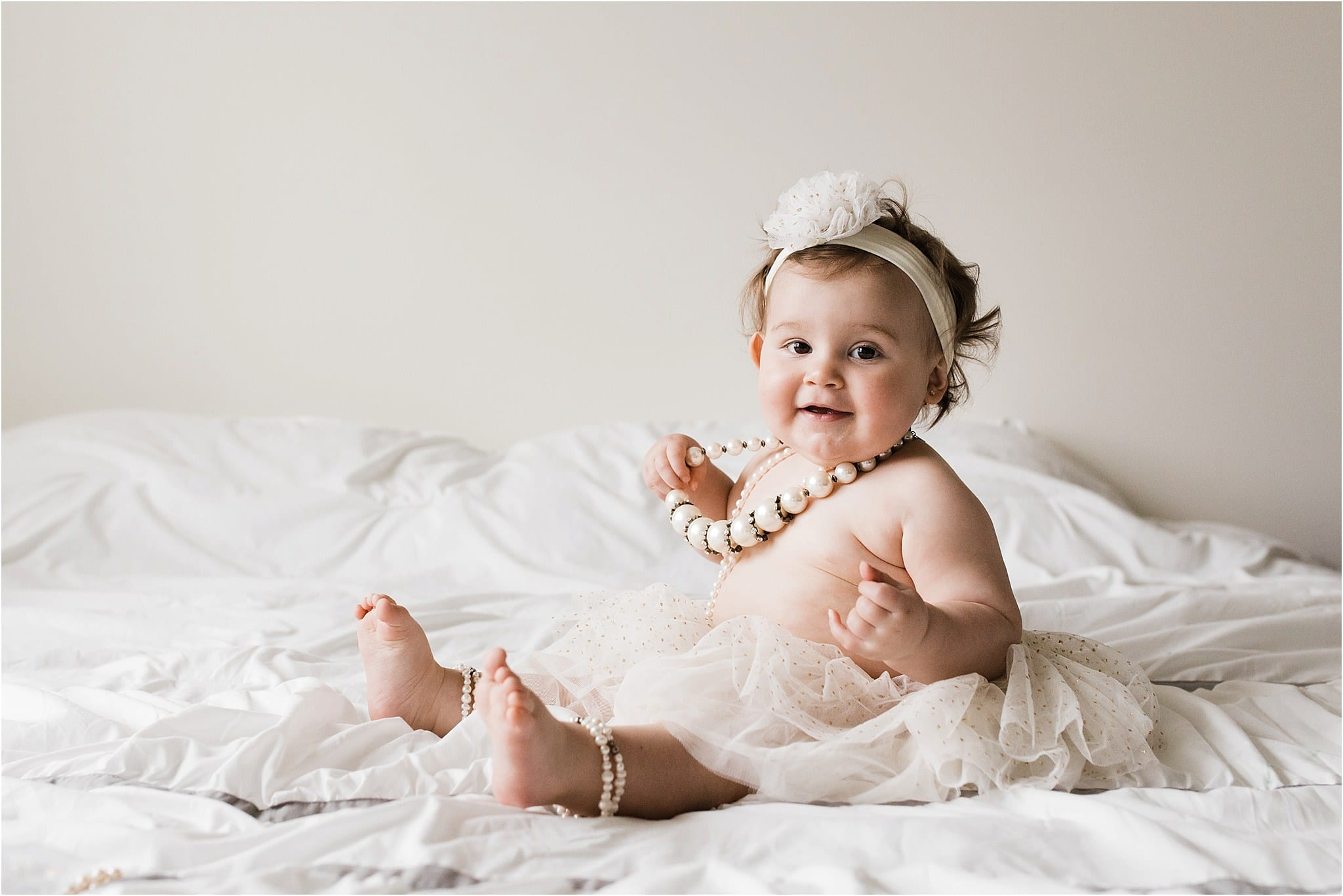 one year old girl wearing grandmothers pearls