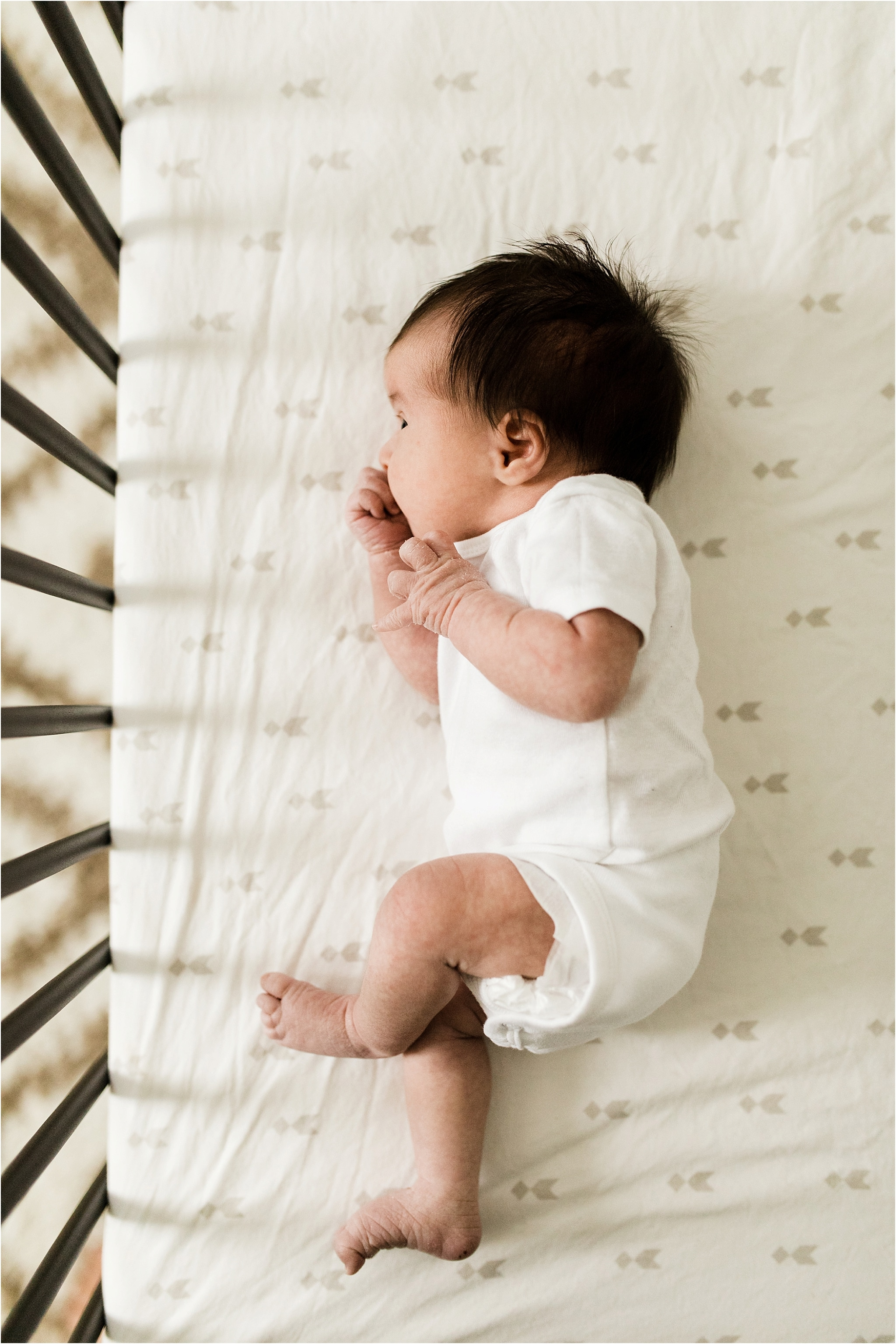 newborn baby in white onesie in crib