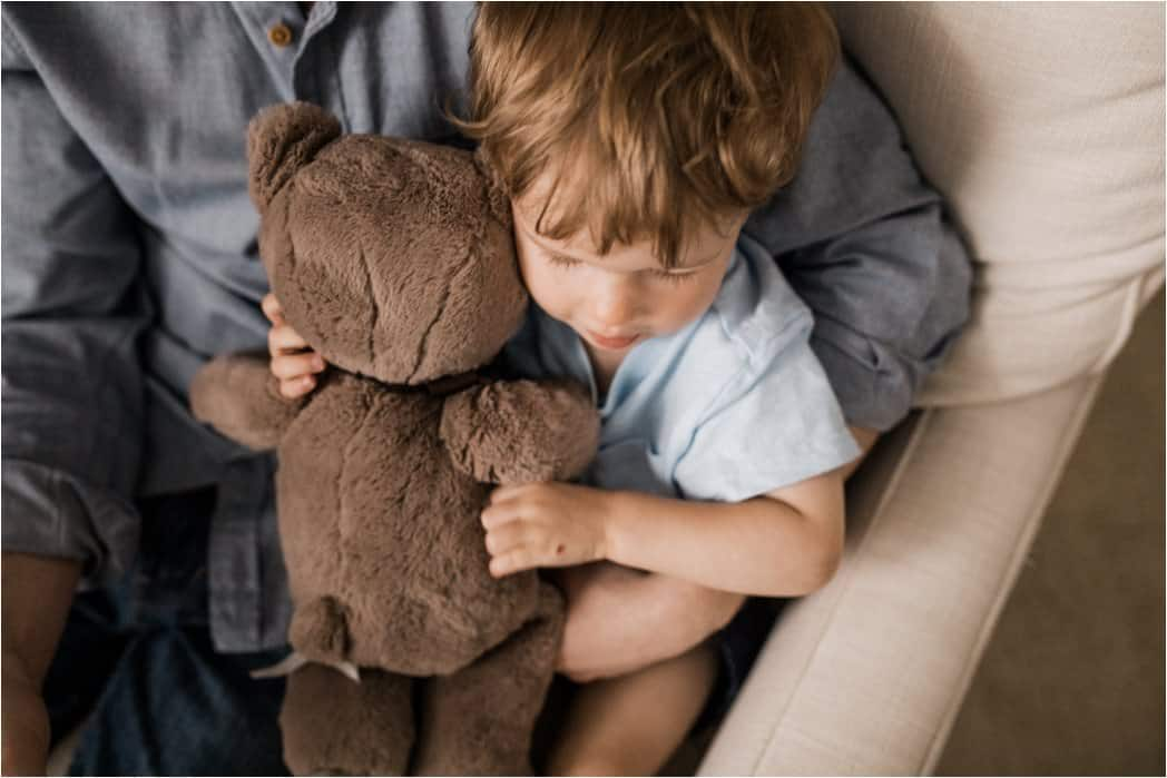 toddler snuggling favorite bear