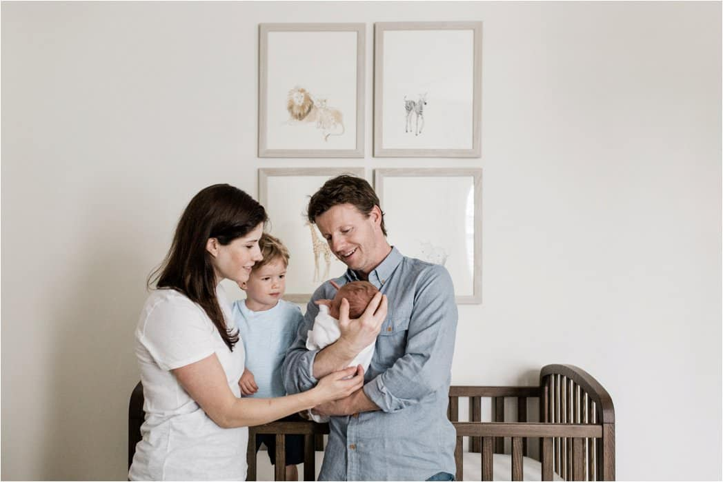 family with newborn in neutral nursery