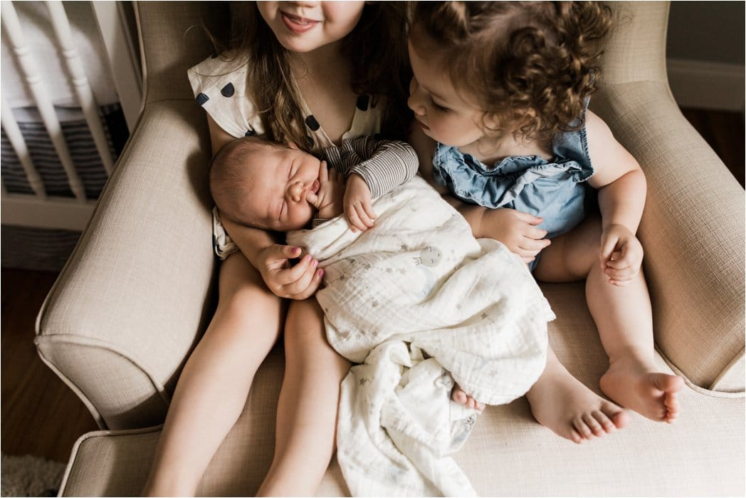 big sisters holding newborn baby bbrother