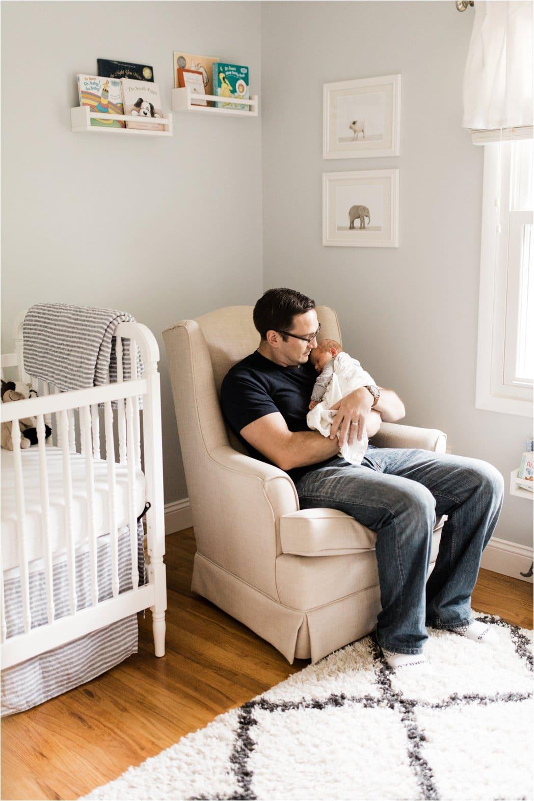 father holding newborn boy in nursery
