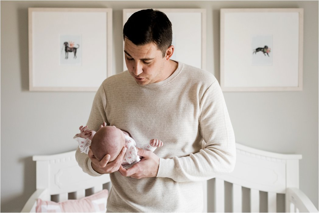 father holding newborn baby girl in nursery