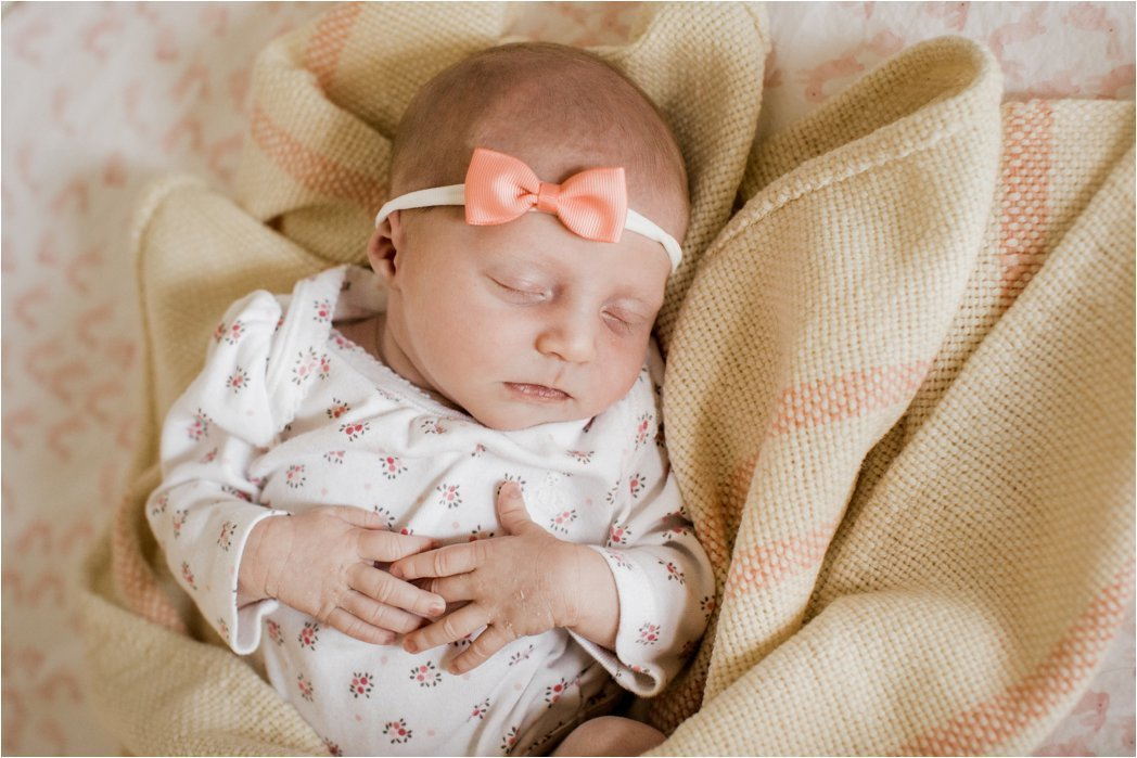 sleeping newborn baby girl in floral onesie and pink bow
