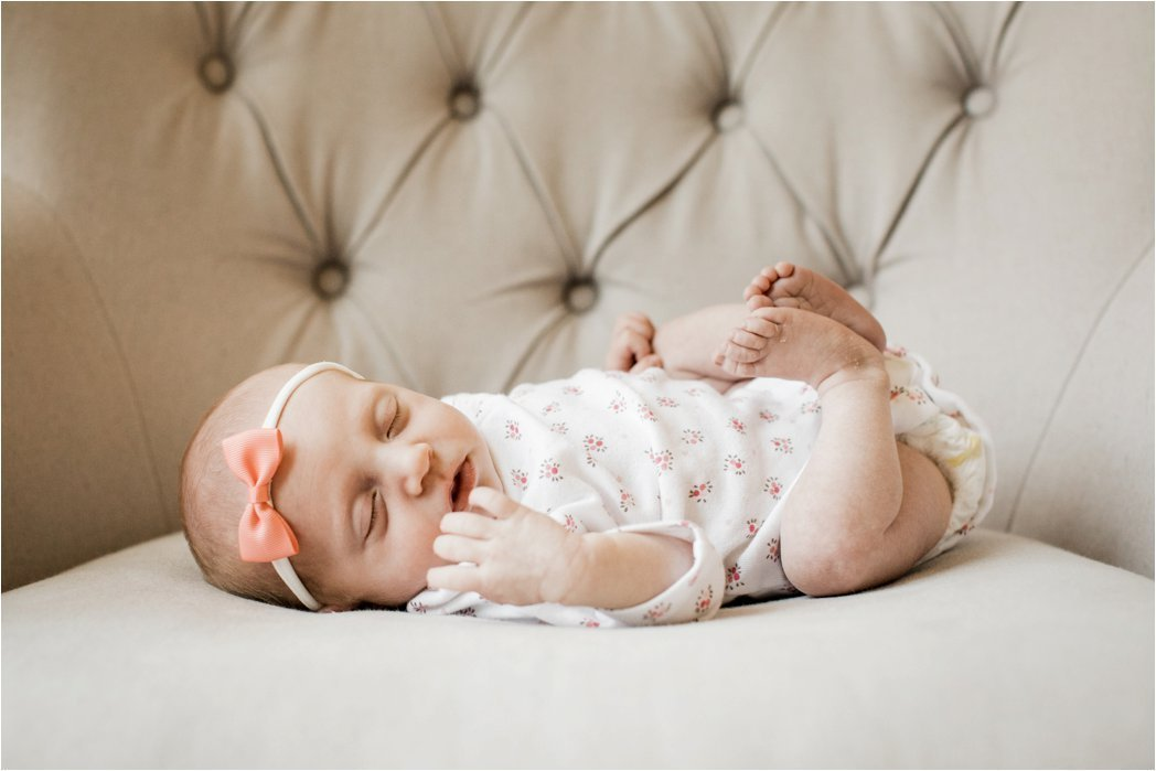 portrait of newborn baby girl in floral onesie and soft pink headband bow
