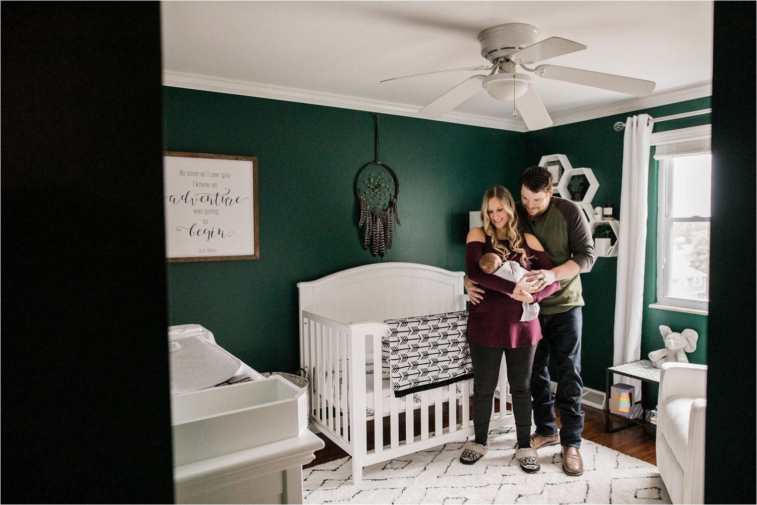 new parents with newborn baby in stylish green nursery with white accents