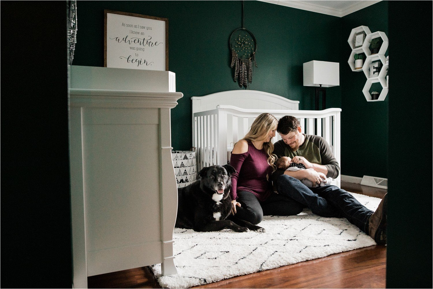 parents hoding newborn with black lab in green and white nursery