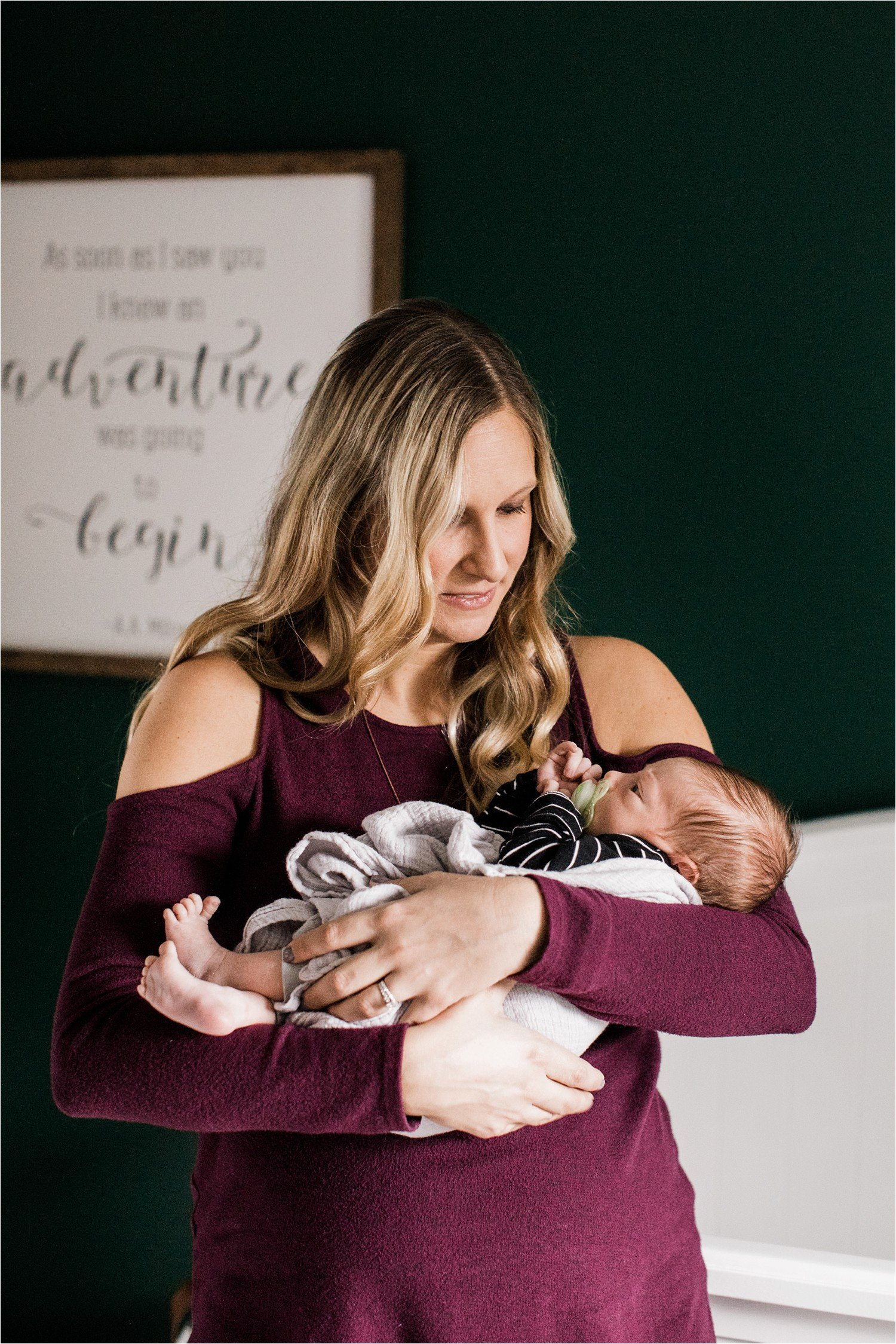 new mother holding baby in green nursery