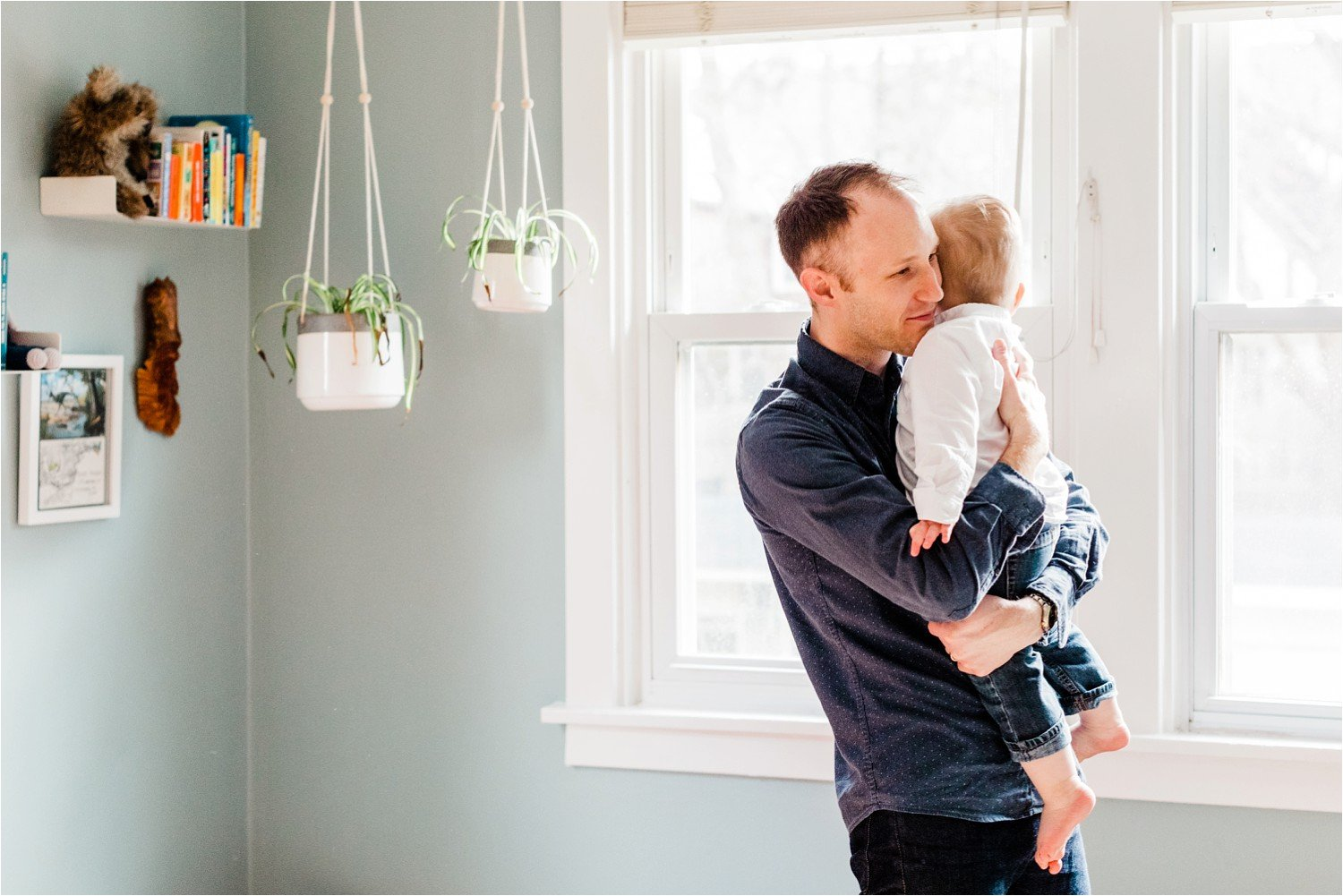 father holding toddler son in childs room
