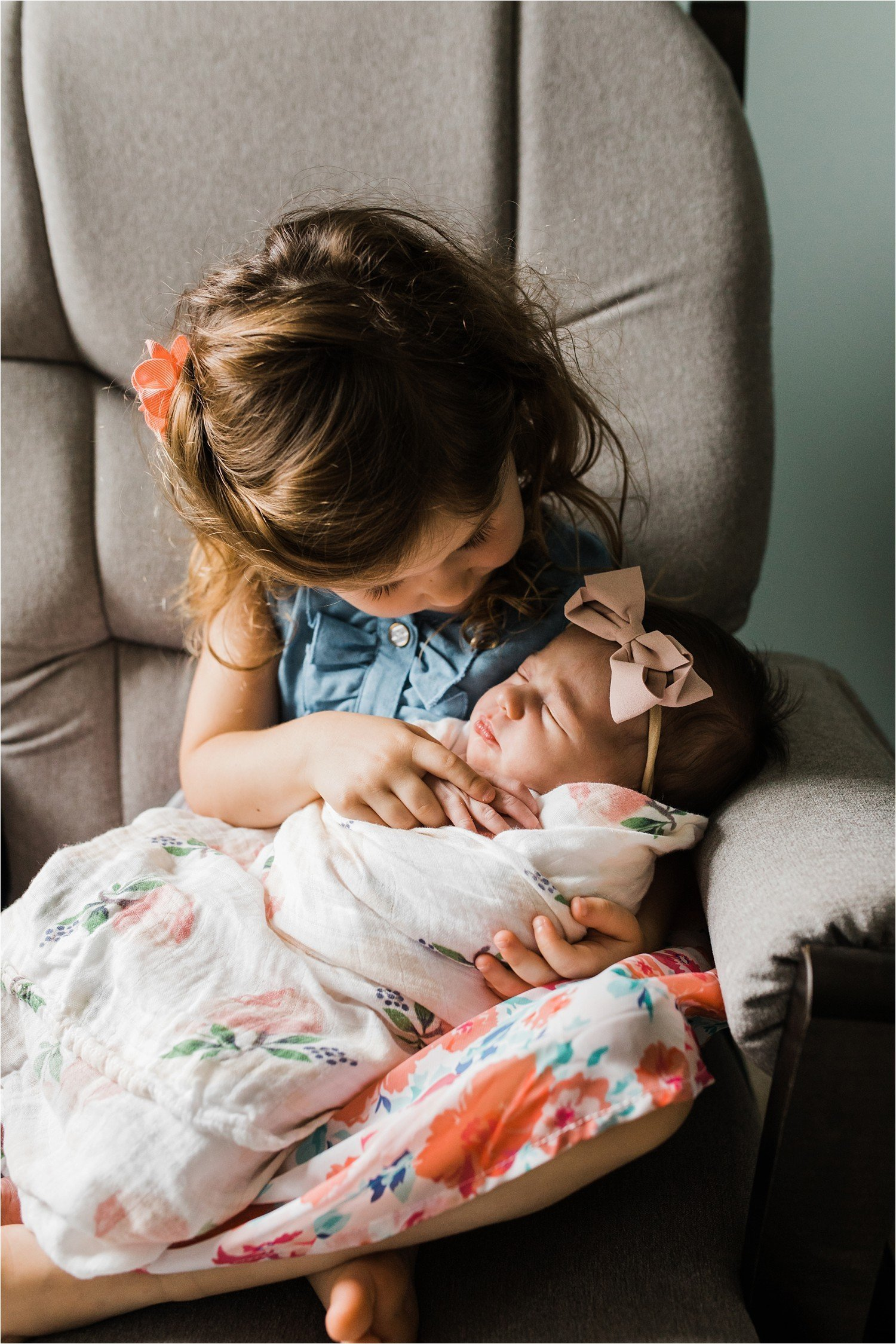 photos of a big sister hold and looking at her new baby sister