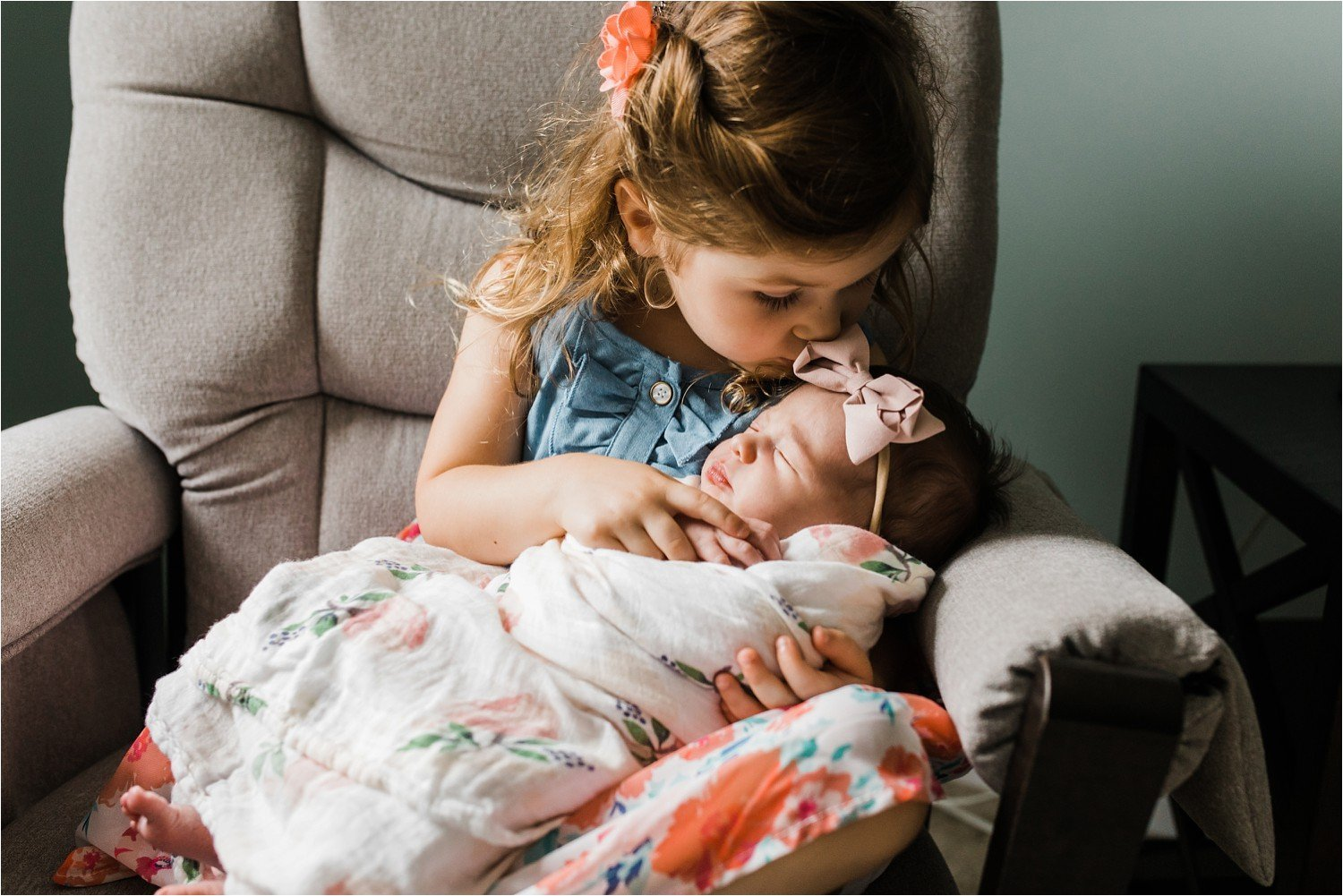 photos of a big sister kissing her new baby sister
