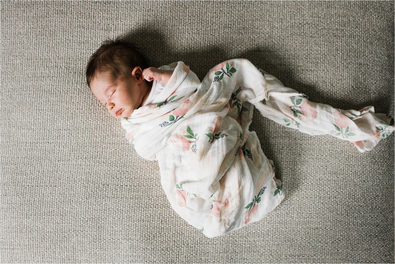 newborn baby girl in a floral swaddle