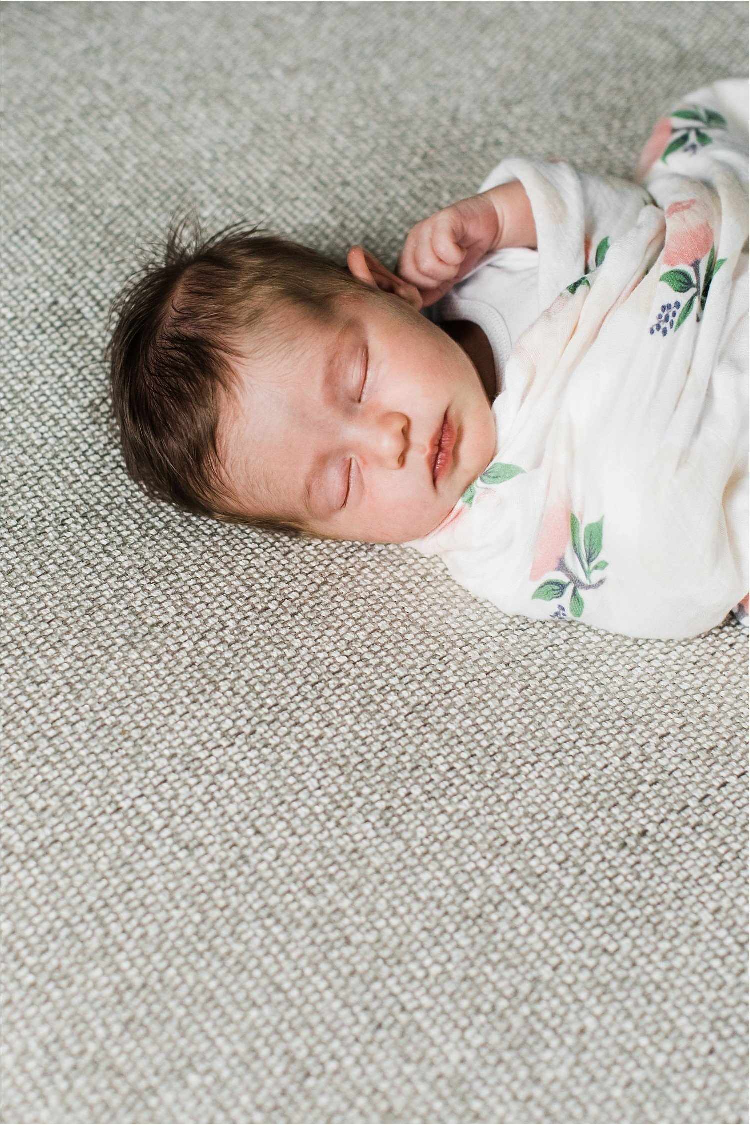 newborn baby sleeping in a floral swaddle