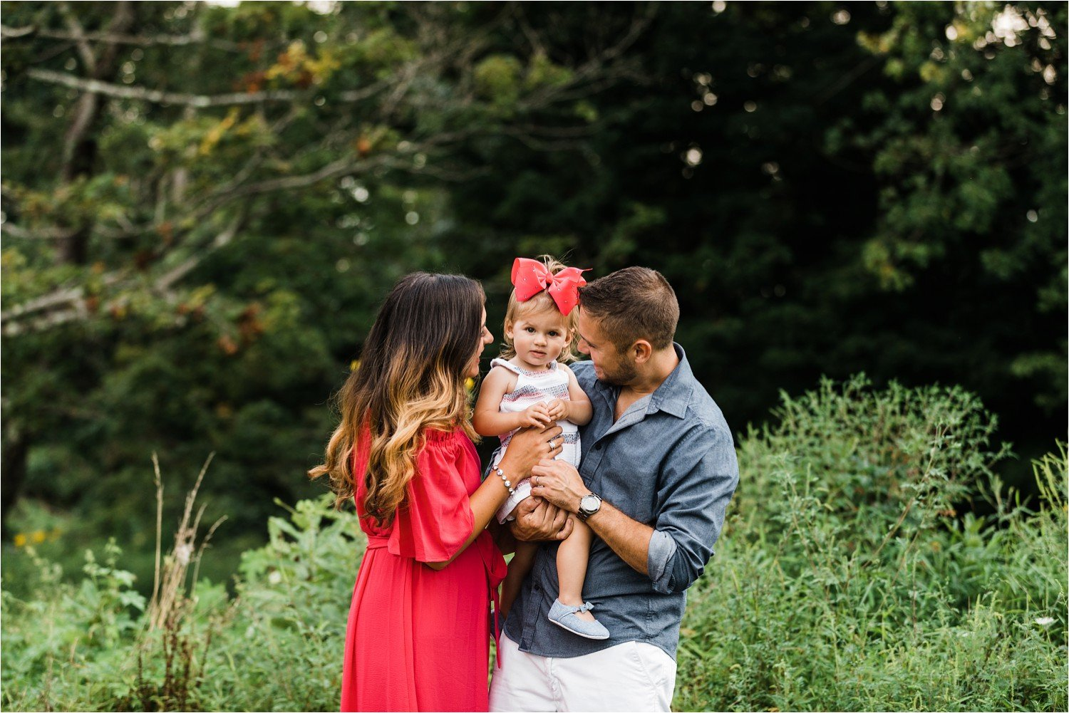 parents kissing toddler girl at family photo session