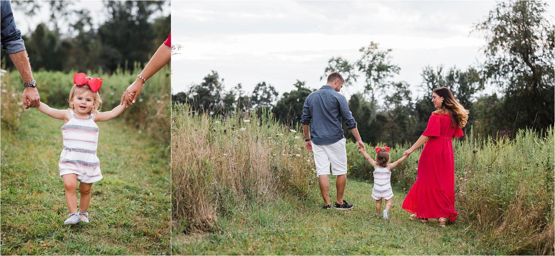 toddler walking between parents holding hands