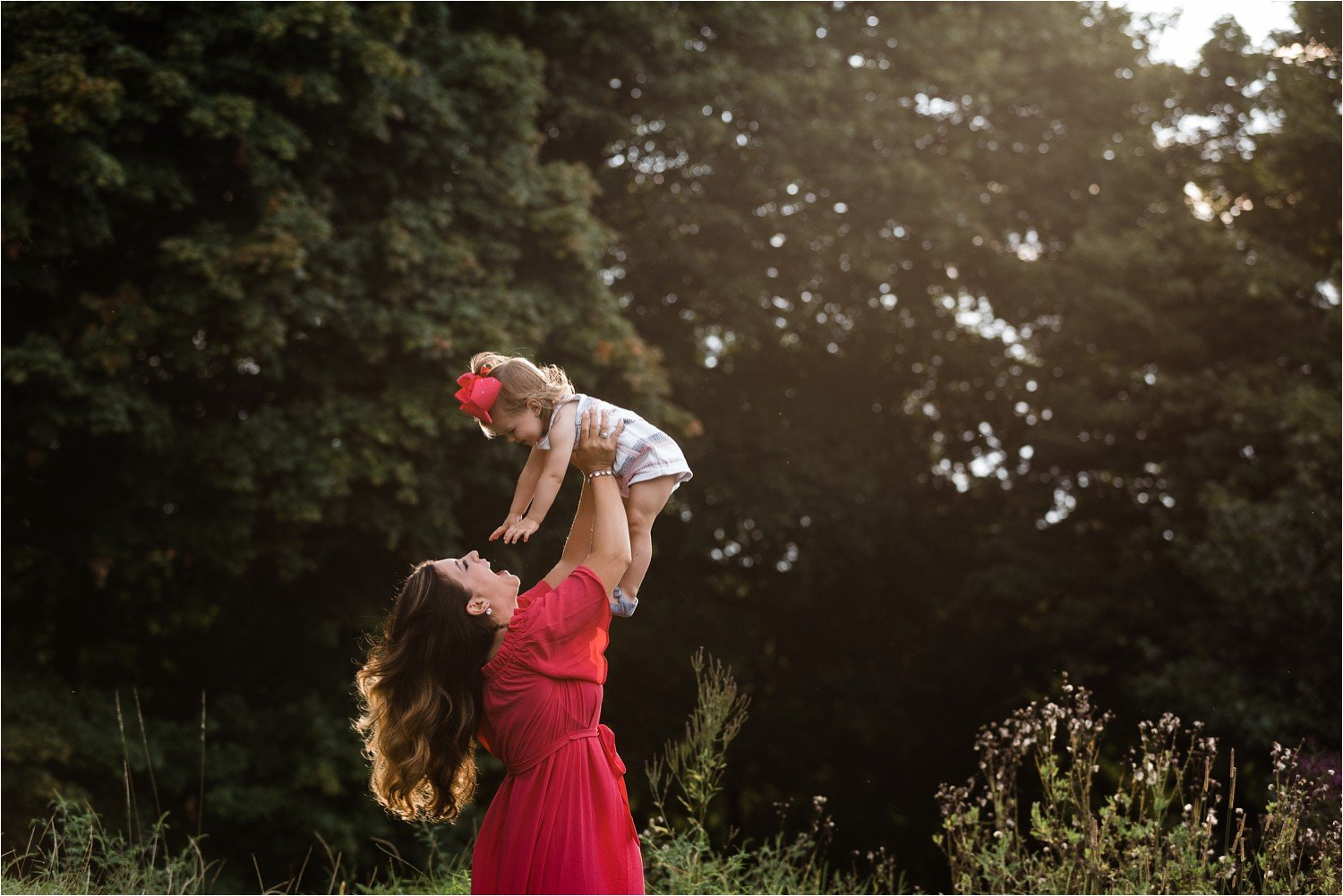 mother holding and dancing with daughter in open field in pittsburgh
