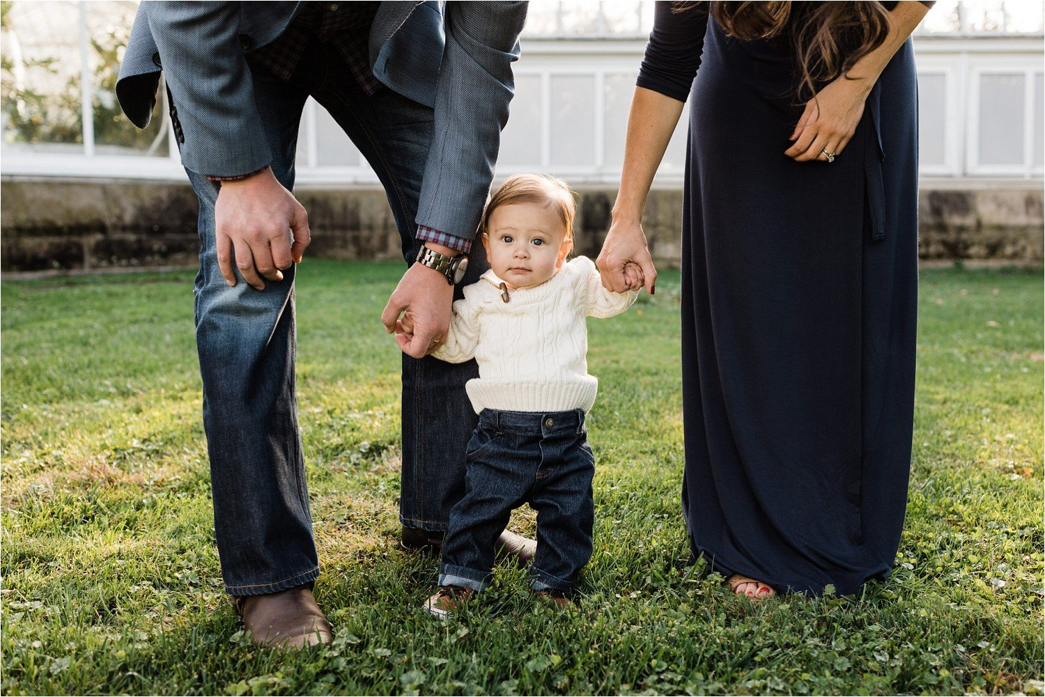6 month old standing between parents holding hands