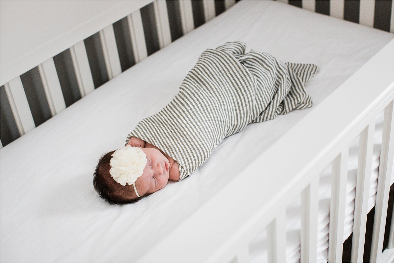 newborn baby girl sleeping swaddled in crib