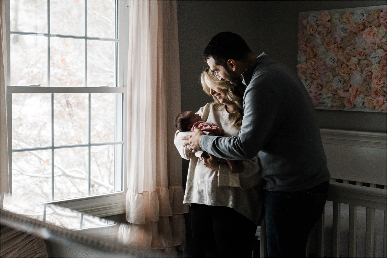 newborn held by parents in hoe nursery