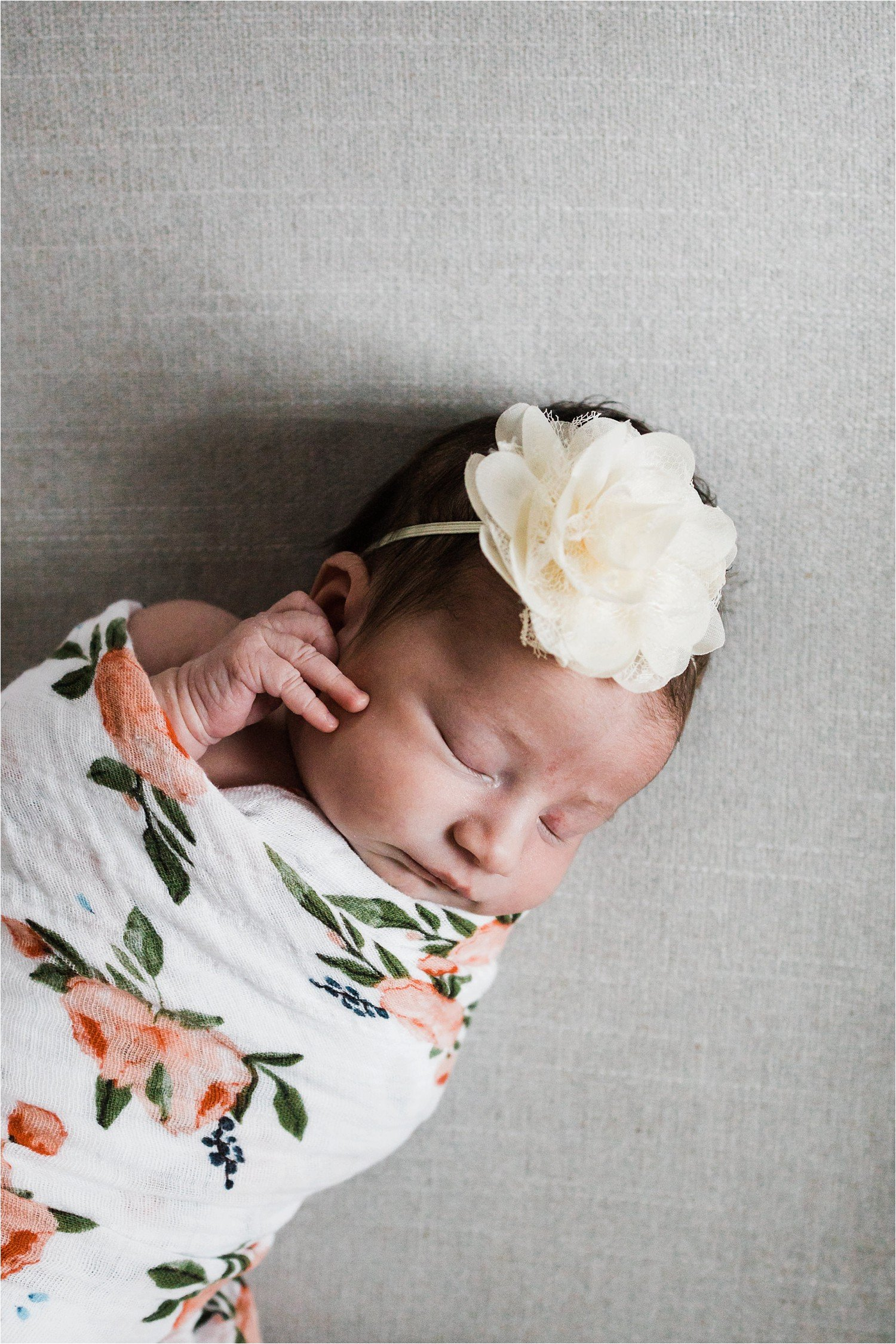 newborn portrait with floral swaddle and flower bow