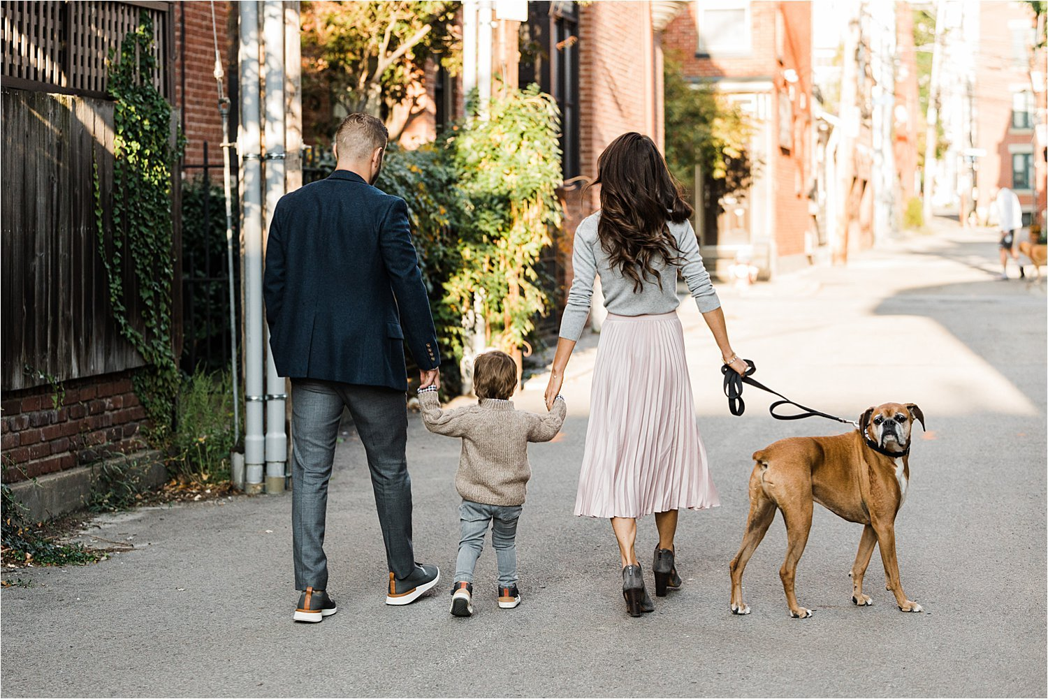 family walking hand in hand with dog