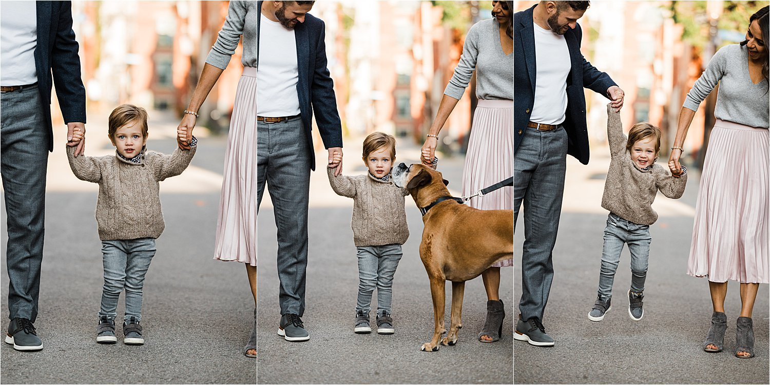 child holding parents hands with family dog