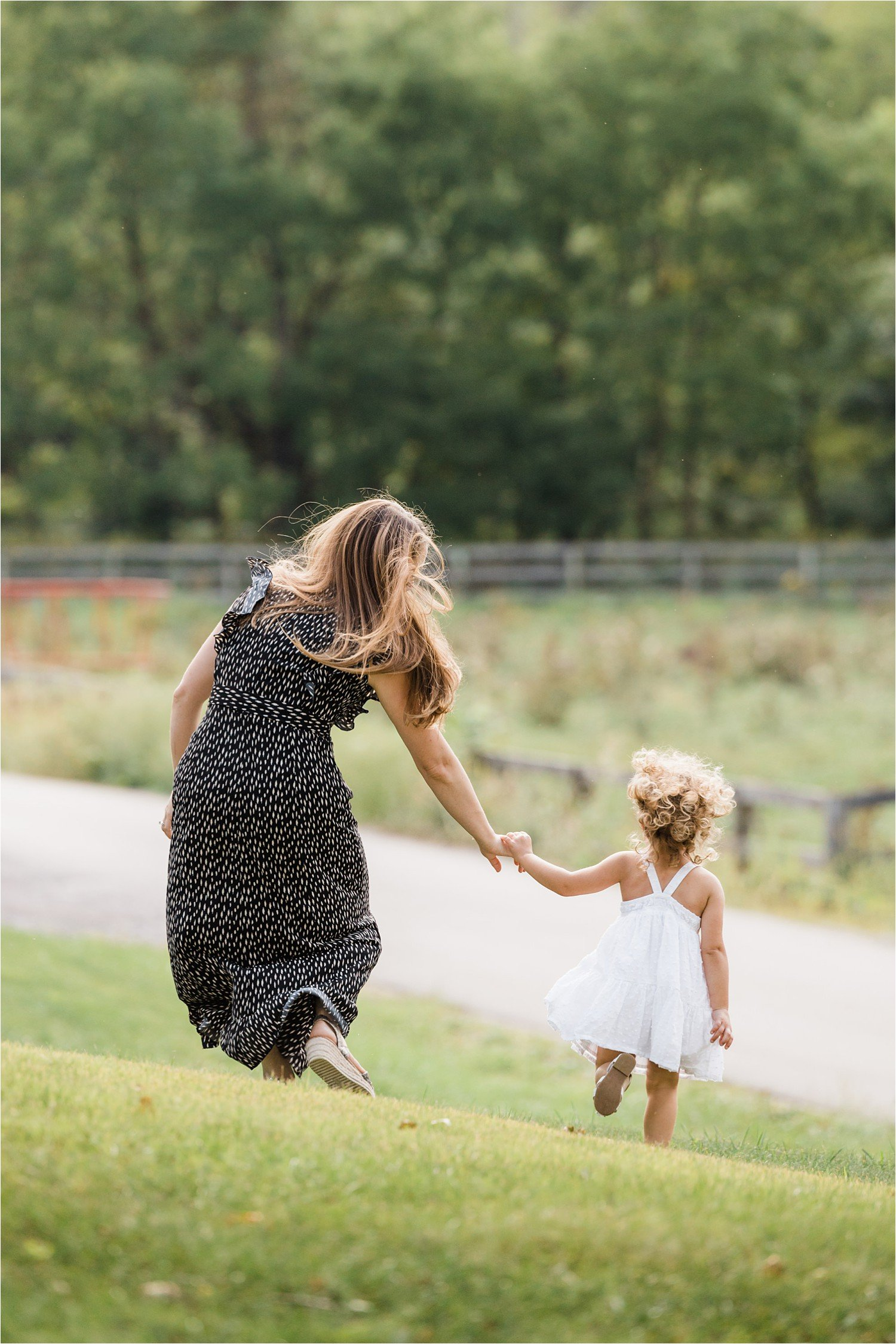 mama and little girl in dresses running and holding hands