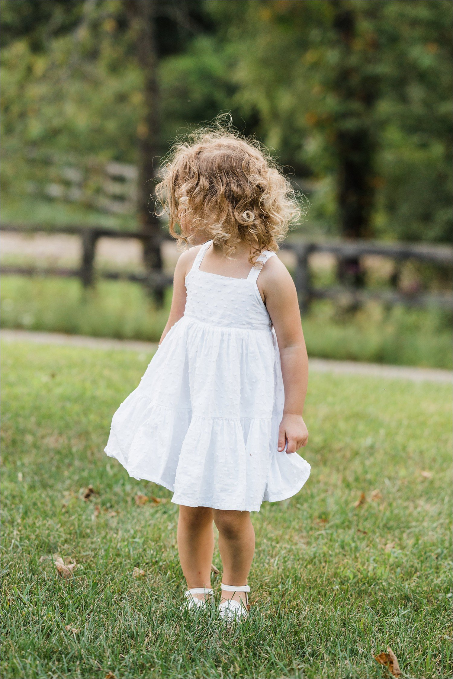 profile portrait of little girl with blonde curly hair in a white dress