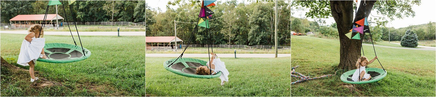 little girl playing on tree swing at home