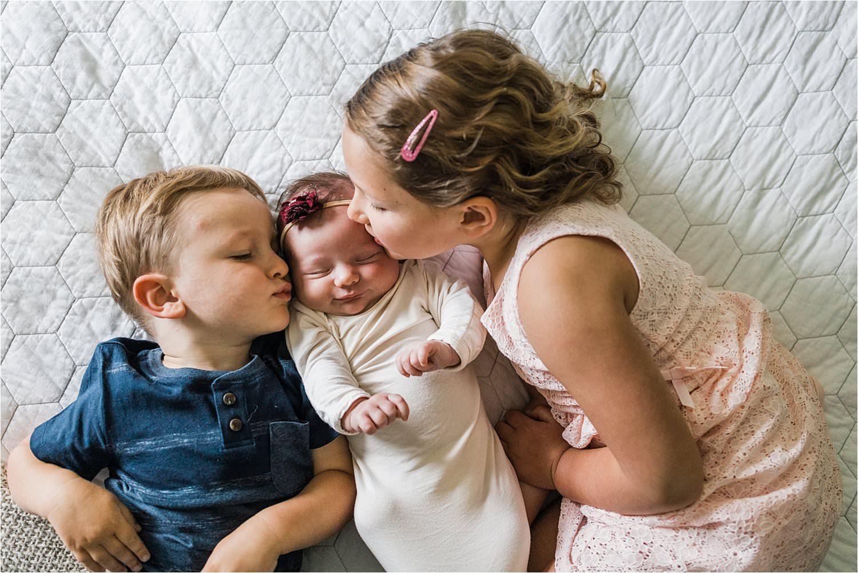 big siblings kissing newborn