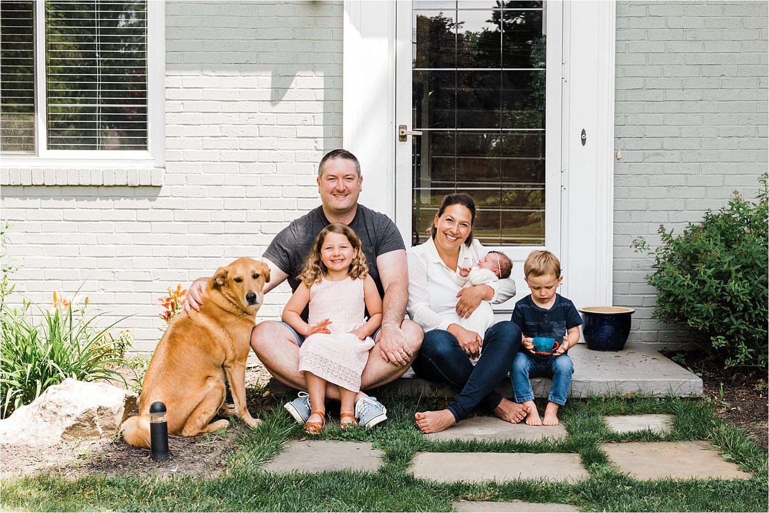 new family photo with dog in front of house