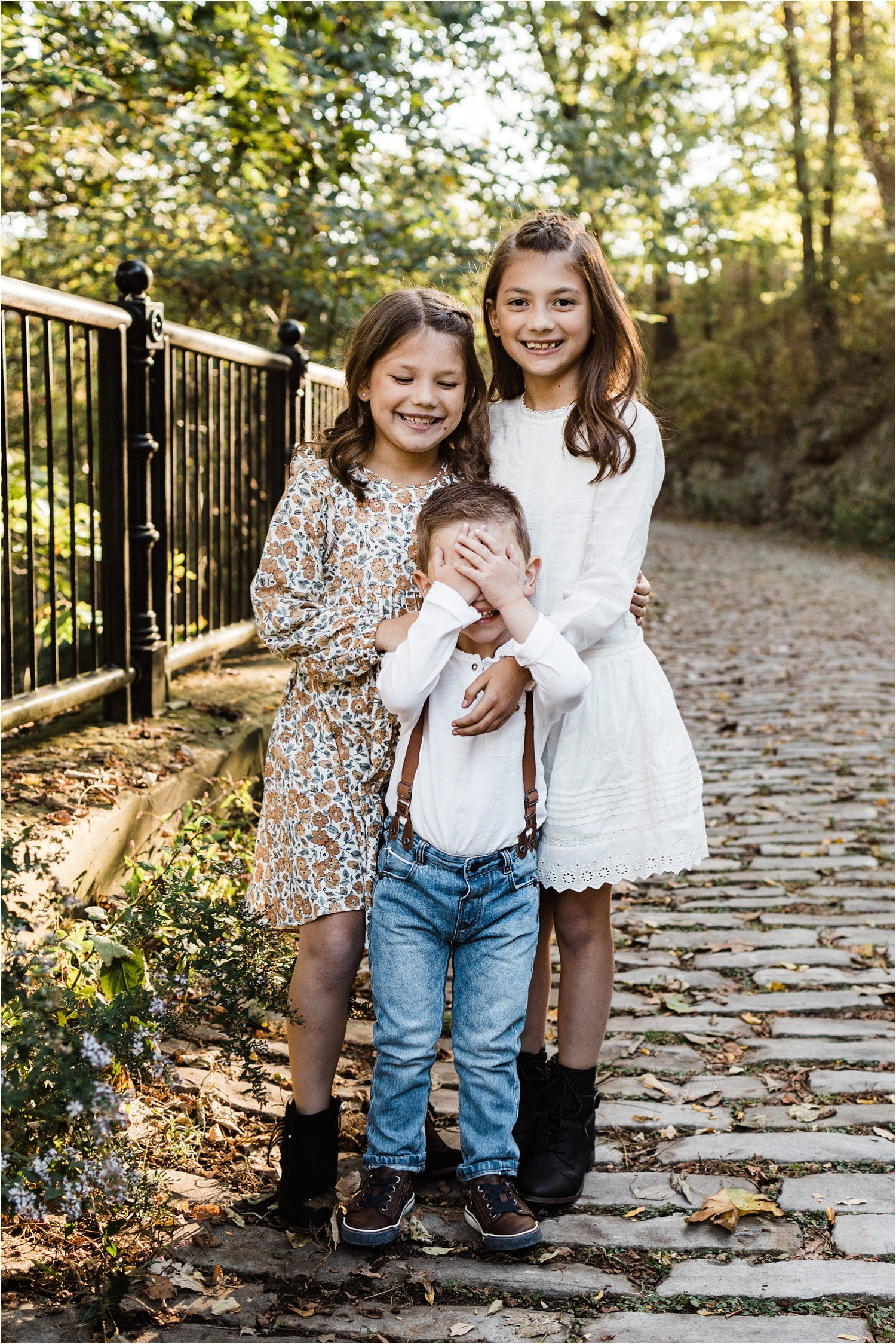 funny boy hiding from camera in a photo with sisters